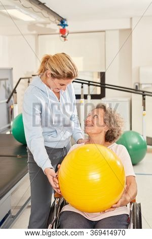 Senior woman and physiotherapist doing exercise with yellow ball