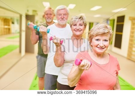 Group of seniors in a fitness class during training with dumbbells to build muscle
