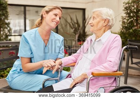 Caregiver takes care of elderly woman in wheelchair in rehab clinic or nursing home