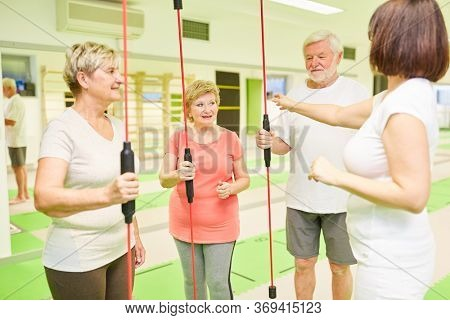 Seniors and fitness trainer with swinging bar for the back training in the fitness center