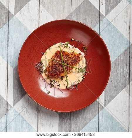 Cod piece with sauce in red deep plate. Fish cooked in tomato crumbs top view. Seafood dish in bowl close-up. Fancy restaurant dish. Art of cooking. Whitefish with batter garnish closeup