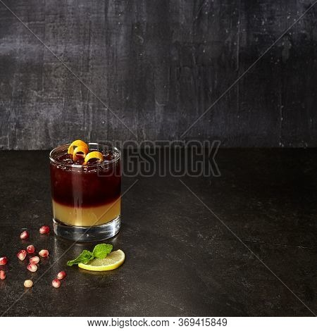 Cocktail with pomegranate and honey. Dark red alcohol drink on black marble table. Glassful of alcoholic concoction with ice cubes Glass of booze. Spirits mixed with juice. Refreshing beverage
