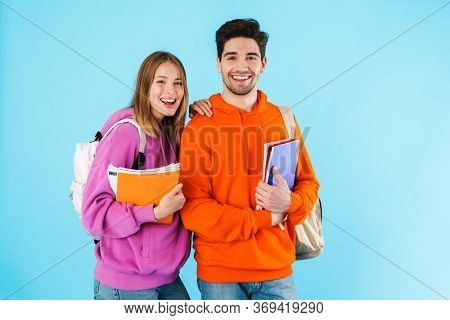 Portrait of a cheerful young couple of students wearing backpacks, carrying textbooks standing isolated over blue background