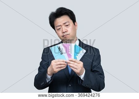 A Middle-aged Asian Businessman Holding A Bank Passbook In His Hand On A Gray Background.