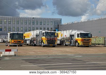 ROTTERDAM AIRPORT, THE NETHERLANDS - CIRCA 2019: BIg fuel trucks parked at an airport, Shell branding. Flying burns large amounts of fossil fuel, significant greenhouse gas emission.