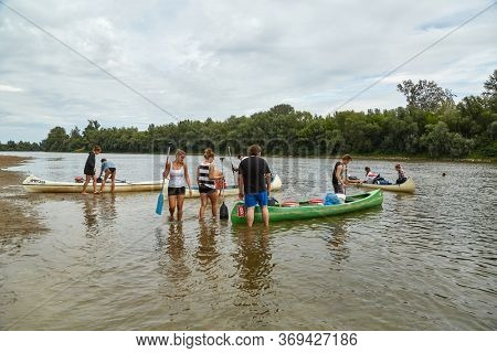 DOMBRAD, HUNGARY - CIRCA 2017: Group of young people preparing for a nomad canoe trip on the river Tisza with canoes ashore. The second larges river of Hungary, popular for water activities.