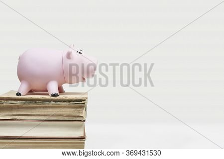 Stack Of Old Books With Piggy Bank. Cost Of Education. Saving Money For College. Save And Pay For Ch