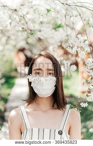 Portrait Of Sad Young Woman In Protective Medical Face Mask With Flowers Near Blooming Tree In Sprin