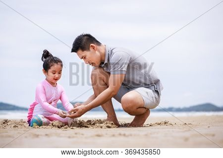 Happy Family. Happy Vacation Holiday. Happy Father And Daughter Are Building A Sandcastle On The Tro