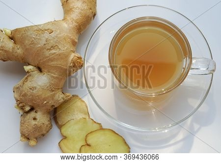Ginger Tea In Glass Cup And Ginger On The Table. Cup Of Hot Ginger Tea And Gingers Root Put On  Tabl