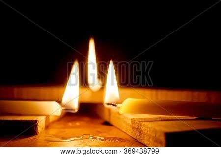 White Candles Burning In The Dark With Lights Glow, The Burning Candle's Flame In The Dark Backgroun