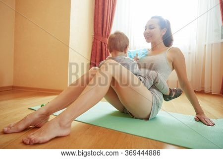 Young Mother Relaxing With Baby After Morning Fitness Workout. Mother Have Fun And Play With Little
