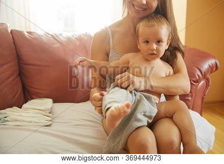 Young Mother Dressing Baby. Caucasian Woman With Beautiful Smile Holding Little Boy On Laps Changing