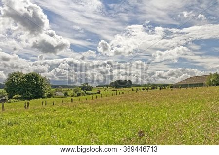 Farms On Sloping Coutryside Surounded By Green Yellow Grass Meadow With A White Cloudy Blue Sky In B