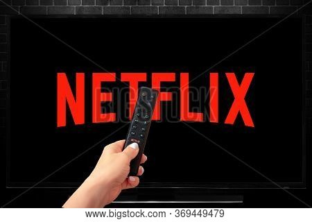 Close Up Of Nvidia Sheild Tv Remote In Hand And Tv Screen With Netflix Logo, Netflix Is A Well Known