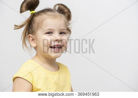 A Little Girl Of 4-5 Years Old In A Yellow T-shirt Laughs. Copy Space To The Right
