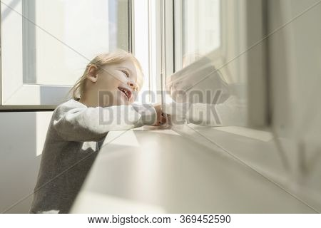 Little Girl Dreamily Looks Out The Window And Smiles. The Sun Illuminates Her Face, Flare. The Child