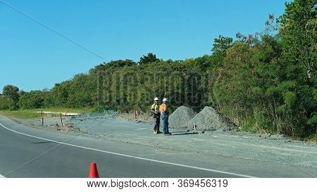 Mackay, Queensland, Australia - June 2020: Two Workers Standing Idle Talking And Surveying A Pile Of