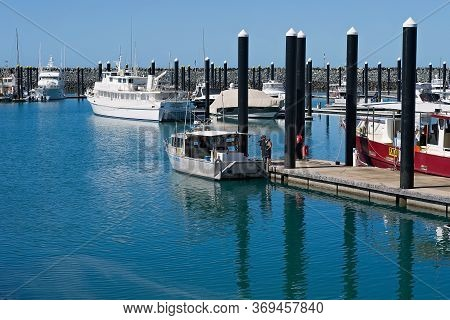 Mackay, Queensland, Australia - June 2020: Three Fishermen Looking At Boat Moored In A Marina Berth