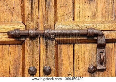 Close-up Of An Old Wooden Door With A Large Wrought Iron Latch And Studs. Verona Province, Veneto, I