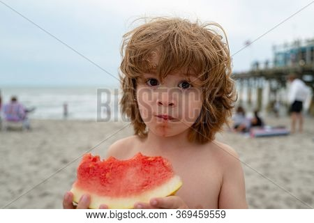 Funny Portrait Of An Incredibly Beautiful Red-haired Little Boy Eating Watermelon. Healthy Fruit Sna