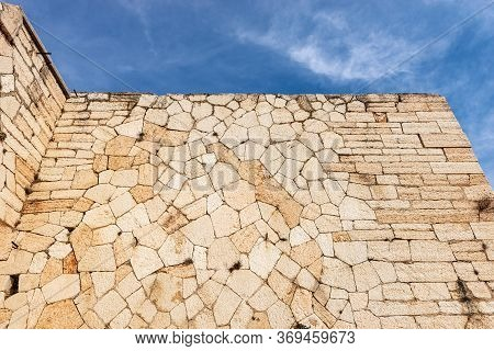 Closeup Of An Austrian Fortified Wall Made Of Irregular Stone Blocks On A Blue Sky With Clouds