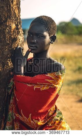 Boya Tribe, South Sudan - March 10, 2020: Young Woman In Colorful Garment Touching Lip And Looking A
