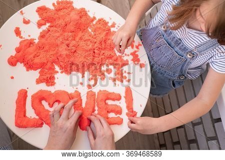 Mom And Daughter Molded Of Red Kinetic Sand The Word Love. The Development Of Fine Motor Skills. Edu