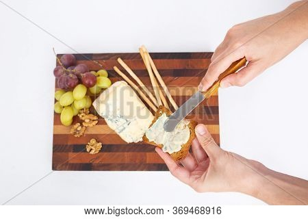 Hands Making Snack Spreading Cheese On Bread. Cutting Board With Cheese, Grape And Walnut On Cutting