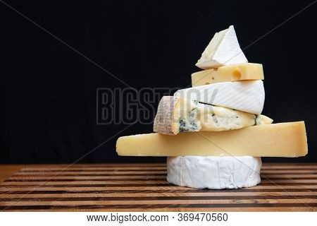 Stack Of Cheeses Standing On Wooden Board. Camembert, Parmesan, Edam. Studio Shot. Side View. Dairy