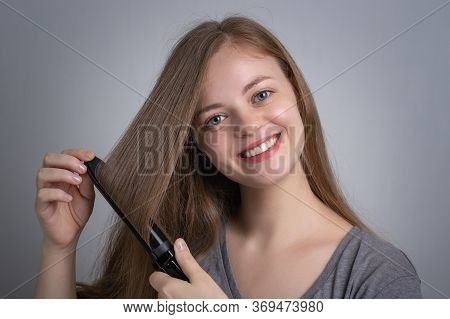 Young Caucasian Woman Girl  Is Straightening Her Long Hair Using Electric Hair Iron Straightener Wit
