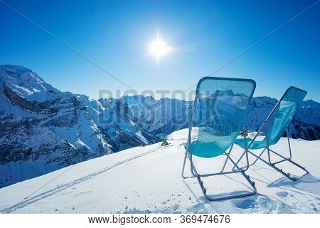 Two Chaise Longue Chairs Stand On The Snow High In The Mountains Over Snowy Summit On Sunny Bright D