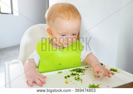Adorable Baby Making Food Messy On Tray While Eating Broccoli Vegetable. Little Child Wearing Plasti