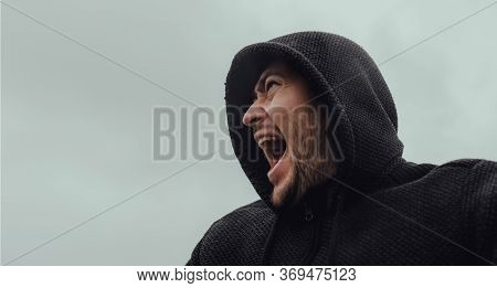 From Below Angry Adult Male In Hoodie Looking Away And Yelling In Rage Against Gray Overcast Sky