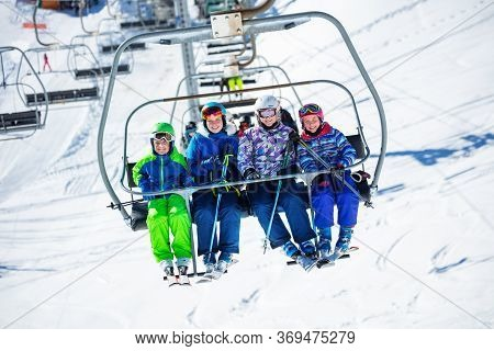 Group Of Skiers Children Sit On Chairlift Going On The Mountain To Ski, Sitting Together Smiling