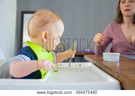 Focused Red Haired Baby Holding Spoon, Trying To Eat By Herself. Little Child Wearing Plastic Bib, S