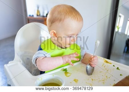Pensive Baby Making Food Mess On Her Tray, Training To Eat With Spoon By Herself. Little Child Weari