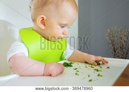 Pensive Baby Studying Pieces Of Broccoli In Her Tray While Eating Vegs. Little Child Wearing Plastic