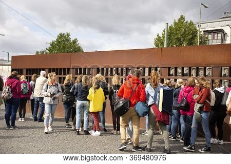 German People And Foreign Travelers Visit Berlin Wall Or Berliner Mauer Guarded Concrete Barrier Cut