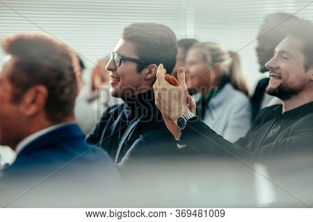 Close Up. A Group Of Young Business People Applaud At A Business Seminar .