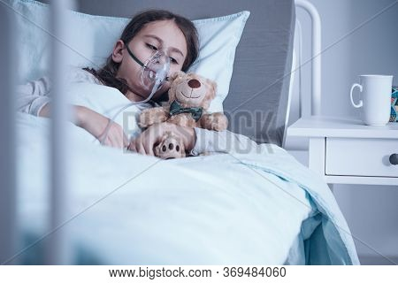 Girl Suffering From Pneumonia Lying In A Hospital Bed With Oxygen Mask And Teddy Bear