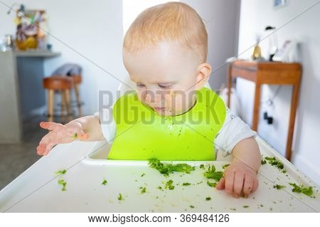 Annoyed Baby Making Broccoli Mess On Her Tray While Eating, Taking Pieces Of Vegs By Hands. Little C