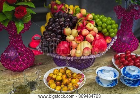 Decorative Glass Porcelain Basket With Ripe Fresh Grapes, Apples And Dragonfruit On A Table In A Chi