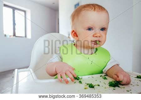Funny Baby Girl Eating Soft Cooked Vegetables By Herself. Little Child Sitting On Highchair And Havi