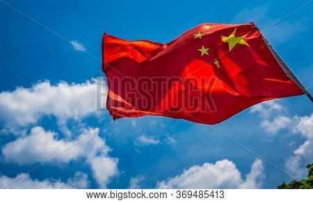 Red Chinese National Flag Fluttering On A Mast With A Blue Sky Background