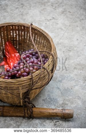 A Vertical Shot Of Fresh Grapes In A Wicker Basket On The Ground