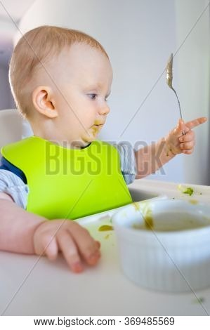 Pensive Baby Learning To Hold Spoon, Eating Vegs And Puree By Herself. Little Child Wearing Plastic