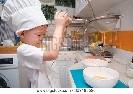 Cute Happy Smiling Asian Little Boy Child Having Fun Cooking Breakfast In Kitchen, Fun Indoor Activi