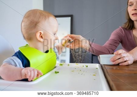 Mom Teaching Baby To Eat With Spoon. Little Child Wearing Plastic Bib, Sitting In Highchair. First S