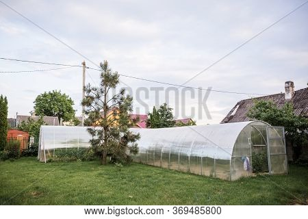 Polycarbonate Greenhouse On A Country Site Cottage Area. Landscaping With A Smart Arrangement Of Obj